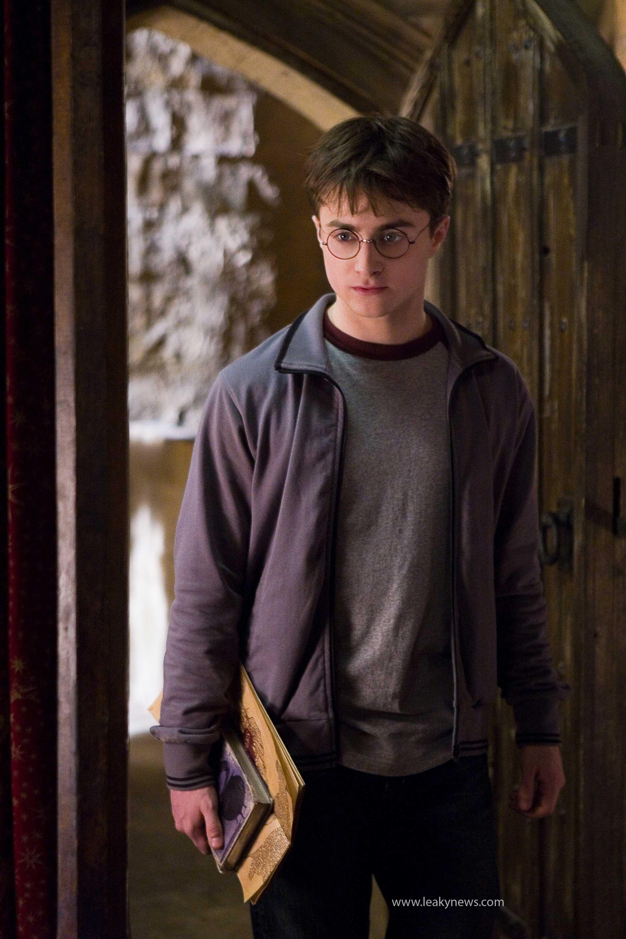 Harry Potter (Daniel Radcliffe) sosteniendo el libro de pociones de El Príncipe Mestizo y el Mapa del Merodeador.
